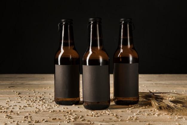 Nahaufnahme von drei bierflaschen und ohren des weizens auf hölzernem hintergrund Kostenlose Fotos