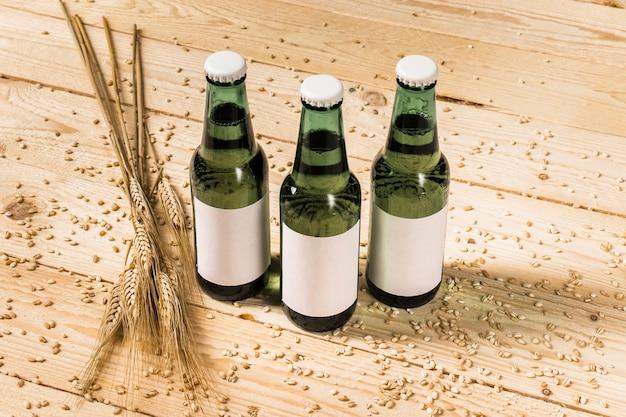Nahaufnahme von drei grünen alkoholischen flaschen und von ohren weizen auf hölzernem hintergrund Kostenlose Fotos