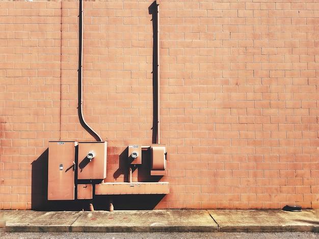 Nahaufnahme von elektrischen sicherungskästen auf einer braunen backsteinmauer Kostenlose Fotos