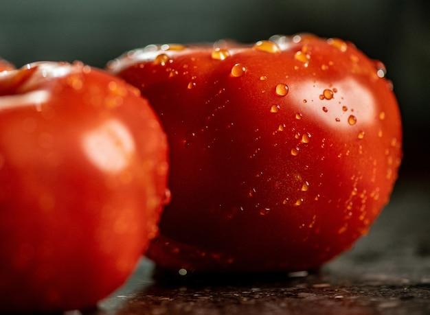 Nahaufnahme von frischen reifen tomaten mit wassertropfen auf einer schwarzen granitküchenarbeitsfläche Kostenlose Fotos