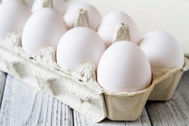 Nahaufnahme von frischen weißen bio-hühnereiern in der papierkassette Premium Fotos