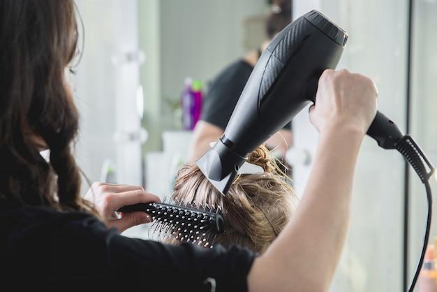 Nahaufnahme von friseurhänden, die langes blondes haar mit föhn und rundbürste trocknen Premium Fotos
