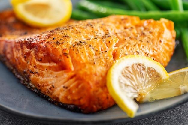 Nahaufnahme von gebackenen lachsfischen mit grünen bohnen Kostenlose Fotos