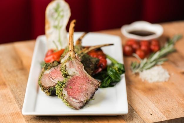 Nahaufnahme von gekochtem rindfleisch mit gewürzen und gebratenen grünen und roten paprikaschoten mit einem unscharfen hintergrund Kostenlose Fotos