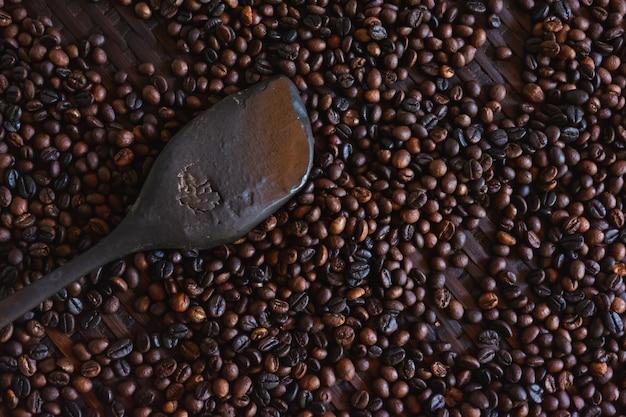 Nahaufnahme von gerösteten kaffeebohnen und holz paddel Premium Fotos