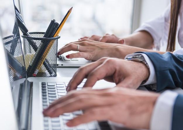 Nahaufnahme von geschäftsleuten händen auf laptop über dem schreibtisch Kostenlose Fotos