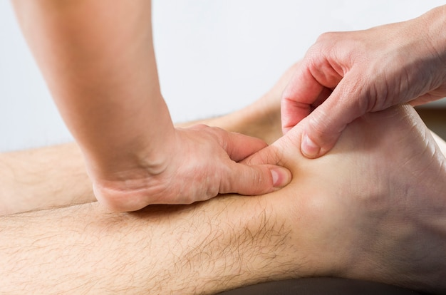 Nahaufnahme von händen des chiropraktikers / des physiotherapeuten, der wadenmuskelmassage tut, um patienten zu bemannen. Premium Fotos