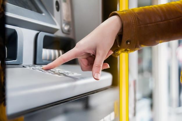 Nahaufnahme von hand eingabe pin an einem geldautomaten. finger, um einen pin-code auf einem pad zu drücken. sicherheitscode auf einem geldautomaten. weibliche arme, atm - einstiegstift Premium Fotos