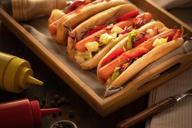 Nahaufnahme von hotdogs mit senf und ketschup, auf rustikalem holz und dunkler art Premium Fotos