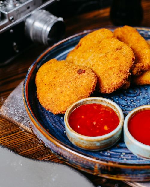 Nahaufnahme von hühnernuggets, die mit süßem chili-saucen-ketchup und mayonnaise auf platte auf dunkelheit serviert werden Kostenlose Fotos