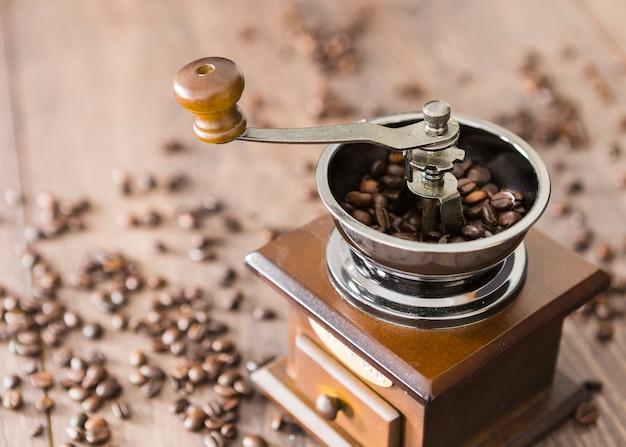 Nahaufnahme von kaffeebohnen mit schleifer Kostenlose Fotos
