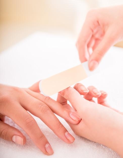 Nahaufnahme von kosmetikerpoliernägeln des weiblichen kunden. Premium Fotos