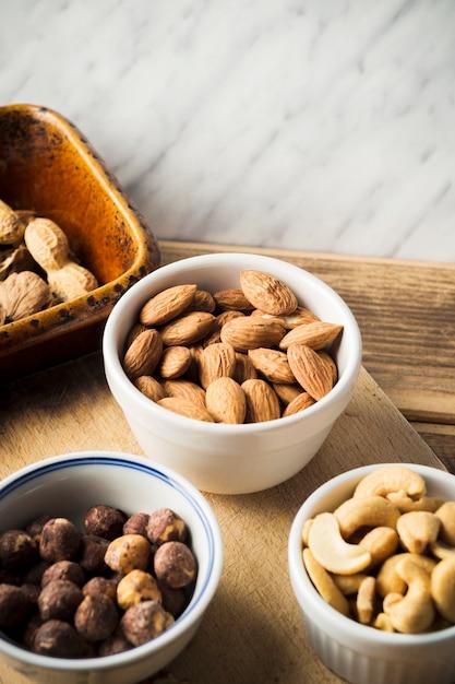Nahaufnahme von mandeln; haselnuss; cashewnuss und erdnüsse in schüssel auf schneidebrett Kostenlose Fotos