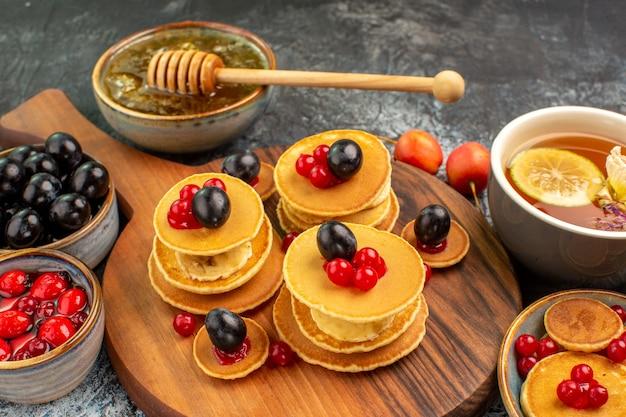 Nahaufnahme von obstpfannkuchen serviert mit honig eine tasse tee Kostenlose Fotos