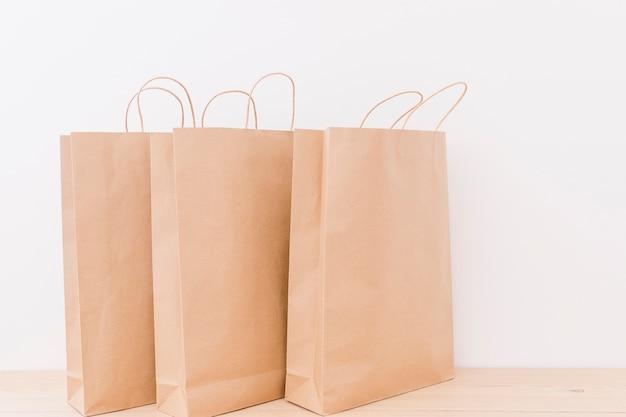 Nahaufnahme von papiereinkaufstaschen auf hölzernem schreibtisch Kostenlose Fotos
