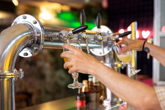 Nahaufnahme von personenhänden, die zwei bierkrüge gleichzeitig in einer bar füllen. selektiver fokus. Premium Fotos