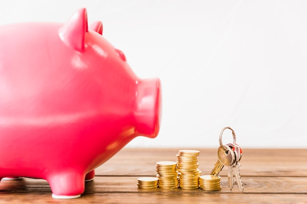 Nahaufnahme von rosa sparschwein nahe staplungsmünzen und -schlüssel Kostenlose Fotos