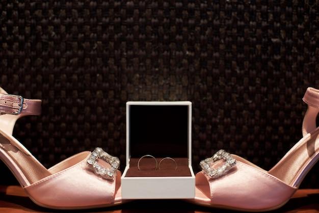 Nahaufnahme von schönen rosa sandalen und von eheringen mit diamanten Premium Fotos