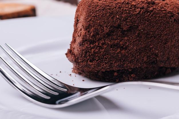 Nahaufnahme von schokoladenkuchen und gabel im vordergrund Premium Fotos
