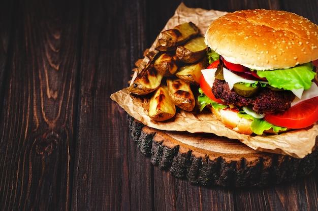 Nahaufnahme von selbst gemachten rindfleischburgern mit kopfsalat und majonäse diente auf wenigem hölzernem schneidebrett. Premium Fotos
