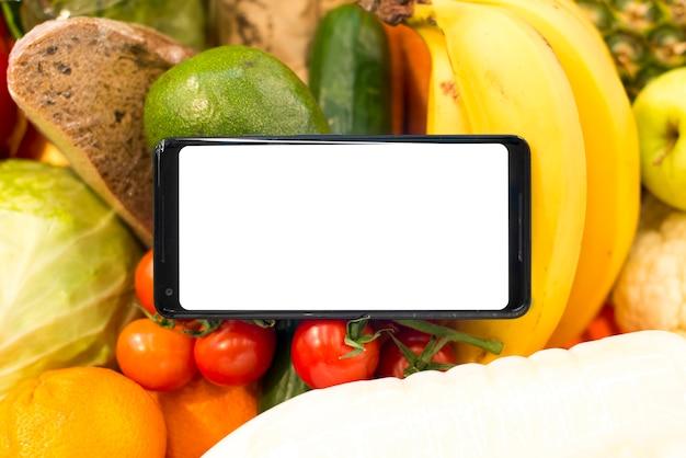 Nahaufnahme von smartphone auf obst und gemüse Kostenlose Fotos