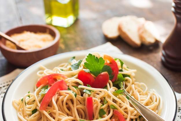 Nahaufnahme von spaghettis mit tomaten und korianderblättern auf platte Kostenlose Fotos