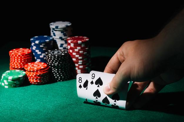 Nahaufnahme von spielkarten einer person auf kasinotabelle Kostenlose Fotos