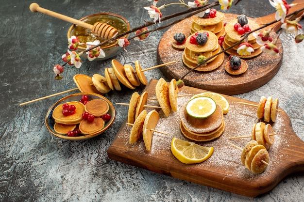 Nahaufnahme von stickigen pfannkuchen auf schneidebrett und honig auf der linken seite des grauen tisches Kostenlose Fotos