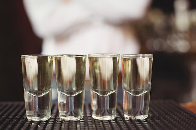 Nahaufnahme von tequila in schnapsgläsern auf bartheke Kostenlose Fotos