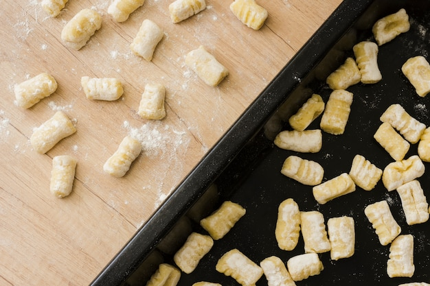 Nahaufnahme von ungekochten selbst gemachten kartoffelgnocchiteigwaren auf backblech und -schreibtisch Kostenlose Fotos
