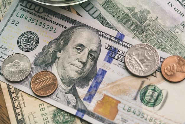 Nahaufnahme von us-dollar währungsgeldbanknoten und -münzen Premium Fotos