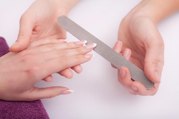 Nahaufnahme von vier weiblichen händen. berufsmanikürist, der nagellack tut. Premium Fotos