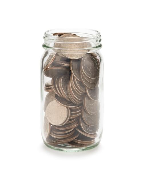 Nahaufnahme von voll von münzen im glas auf weißem hintergrund. isoliert mit beschneidungspfad foto und sparendes investitionskonzept. Premium Fotos