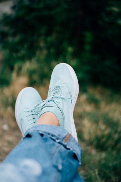 Nahaufnahme von weiblichen beinen in den jeans und in den turnschuhen auf einem hintergrund von bäumen Premium Fotos