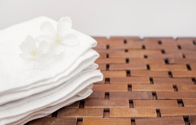 Nahaufnahme von weißen blumen und von tuch auf hölzerner tischplatte Kostenlose Fotos