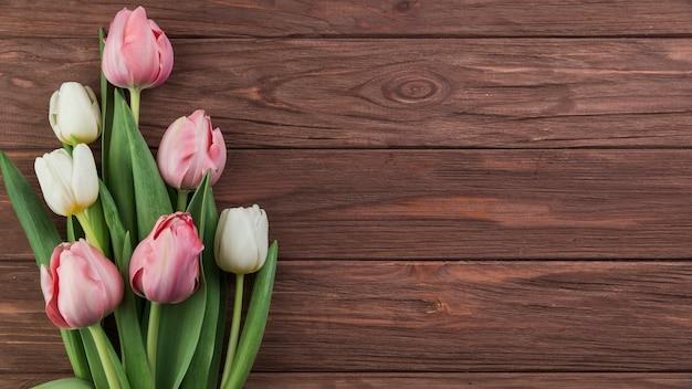 Nahaufnahme von weißen und rosa tulpen auf hölzernem strukturiertem hintergrund Kostenlose Fotos