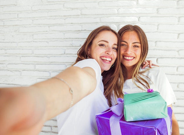 Nahaufnahme von zwei glücklichen freundinnen mit geburtstagsgeschenken Kostenlose Fotos