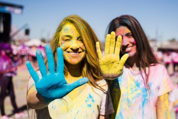 Nahaufnahme von zwei jungen frauen, die ihre gemalten hände mit holi farbe zeigen Kostenlose Fotos