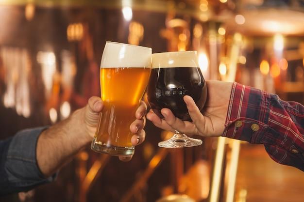 Nahaufnahme von zwei männern, die biergläser zusammenstoßen und in der bierkneipe feiern Premium Fotos