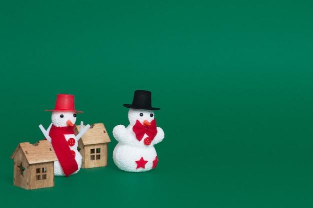 Nahaufnahme von zwei schneemännern und kleinen holzhäusern als weihnachtsschmuck auf grünem hintergrund Kostenlose Fotos