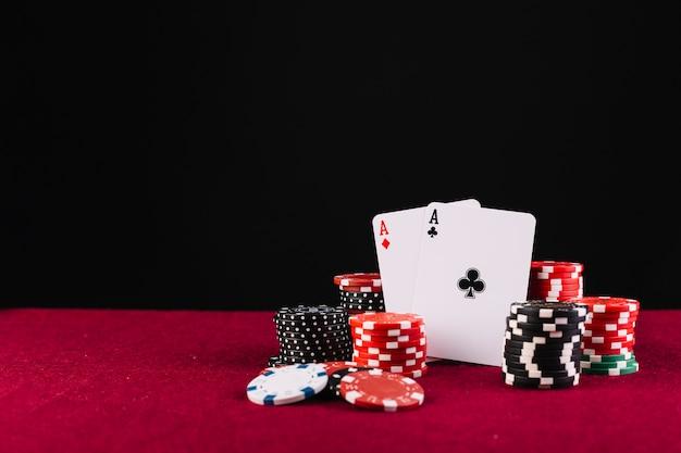 Nahaufnahme von zwei spielkarten und schürhakenchips der asse auf rotem hintergrund Kostenlose Fotos