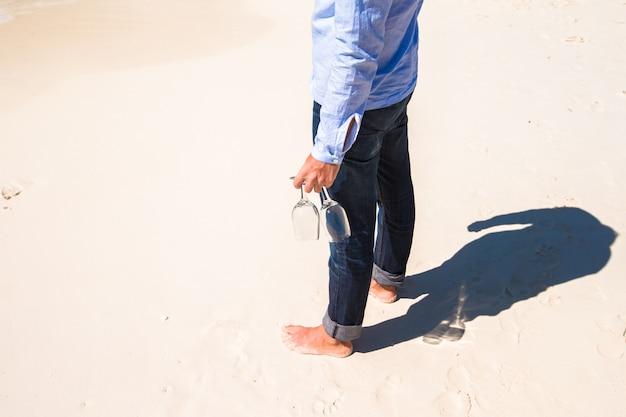 Nahaufnahme von zwei weingläsern in der hand eines mannes auf dem weißen sandigen strand Premium Fotos