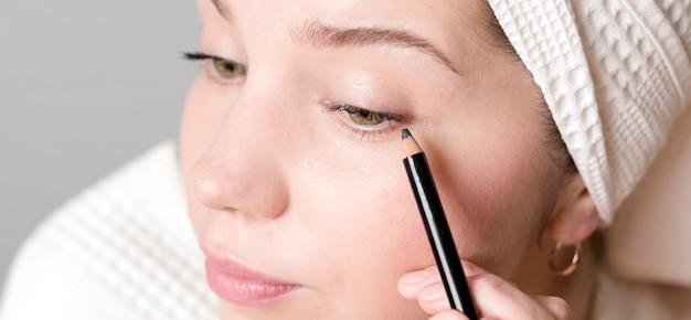 Nahaufnahme weiblich, das eyeliner anwendet Kostenlose Fotos