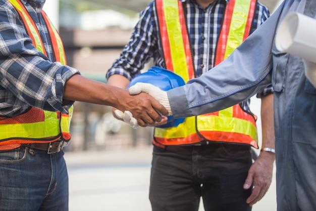 Nahaufnahme zwei ingenieure, die hand rütteln, nachdem ein geschäftstreffen beendet worden ist Premium Fotos
