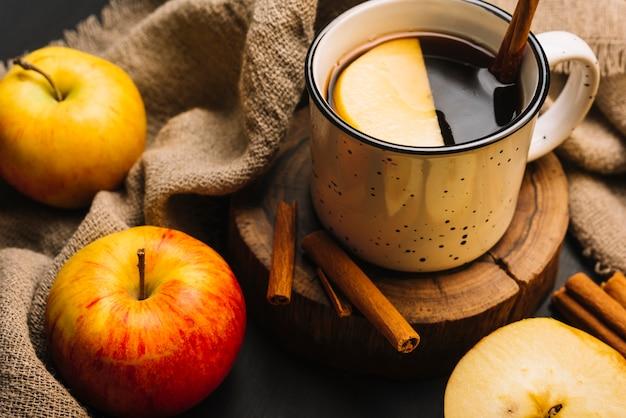 Nahaufnahmeäpfel und -gewebe nahe gewürztem getränk Kostenlose Fotos