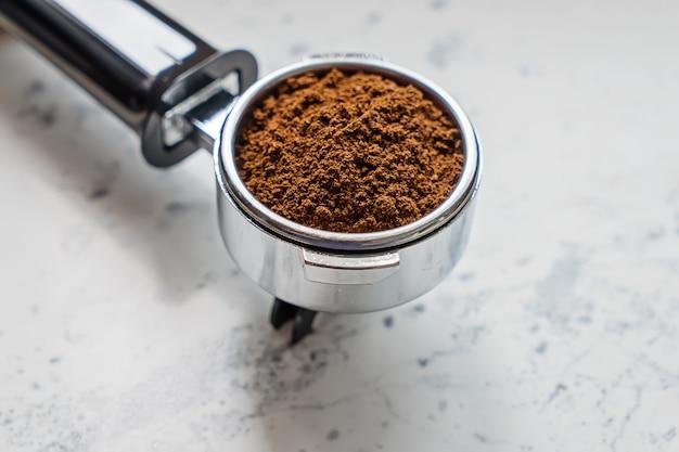 Nahaufnahmeansicht des siebträgers mit gemahlenem kaffee für kaffeemaschine barista Premium Fotos