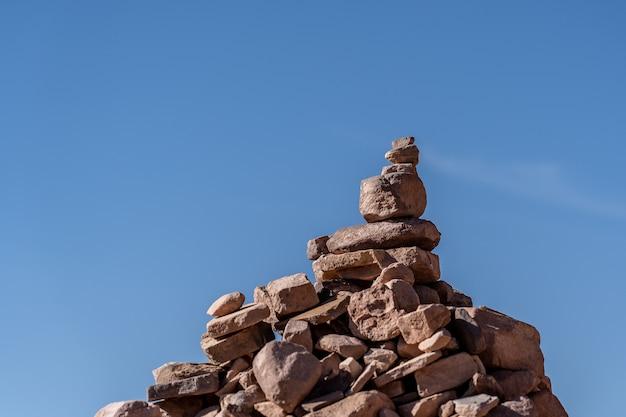 Nahaufnahmeaufnahme der aufeinander gestapelten steine mit blauem hintergrund Kostenlose Fotos