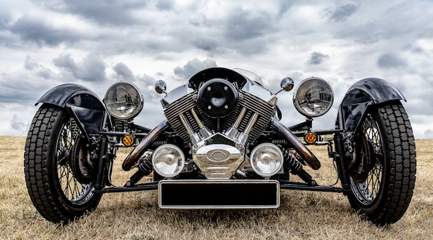 Nahaufnahmeaufnahme der front eines schwarzen fahrzeugs, das auf einem trockenen feld unter einem bewölkten himmel geparkt wird Kostenlose Fotos