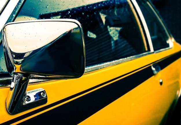 Nahaufnahmeaufnahme der seite eines gelben autos mit einer schwarzen linie unter den fenstern Kostenlose Fotos