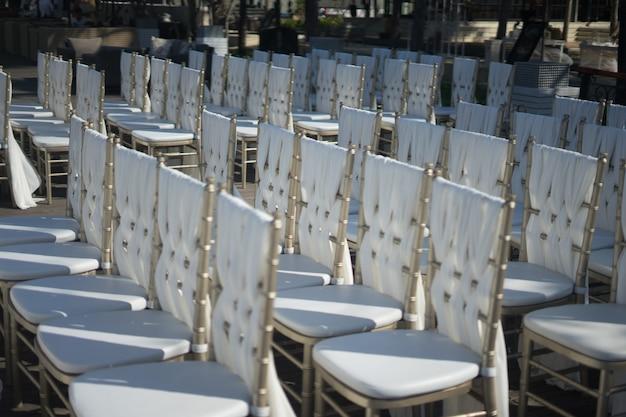 Nahaufnahmeaufnahme der weißen stühle für die gäste einer hochzeitszeremonie Kostenlose Fotos
